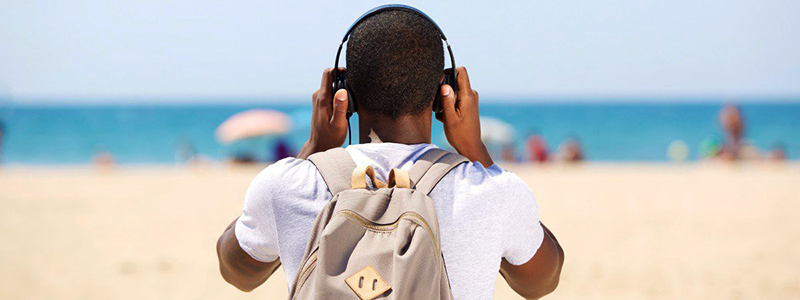 Guy listening to headphones on beach
