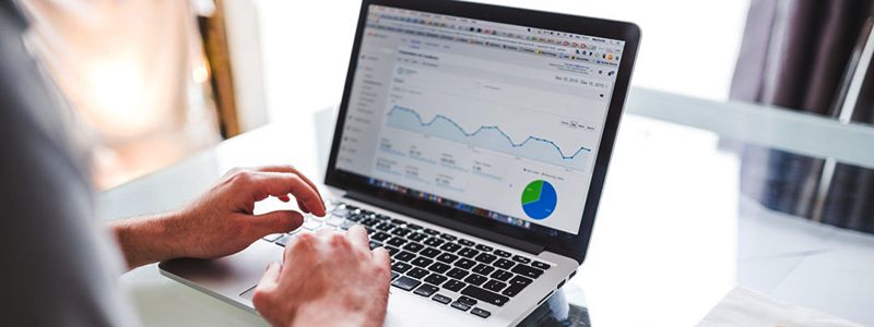 Man using Google Analytics on laptop to help with keyword research